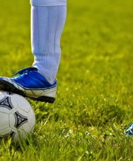 picture of soccer player on field with cleat on soccer ball